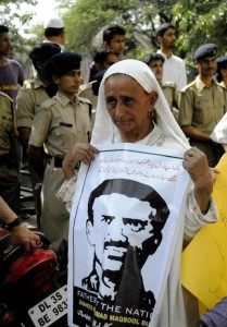 Maqbool Bhat's mother, holding a picture of her dead son at a protest on May 3 in Delhi.